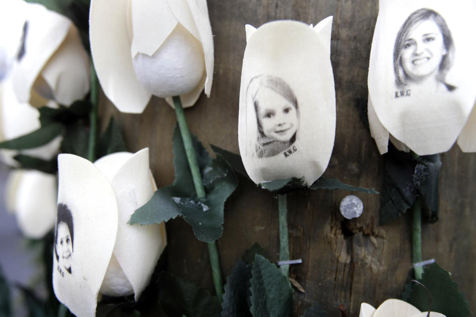 Photos showing those killed in the shootings at Sandy Hook Elementary School are imprinted on fake roses at a memorial in the Sandy Hook village of Newtown, Conn., Saturday, Dec. 22, 2012. (AP Photo/Seth Wenig)