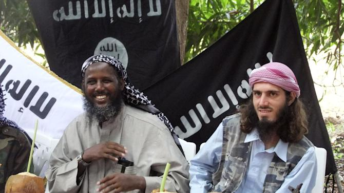 "FILE - In this Wednesday, May 11, 2011 file photo, American-born Omar Hammami, also known as Abu Mansur al-Amriki, right, and deputy leader of al-Shabab Sheik Mukhtar Abu Mansur Robow, left, sit under a banner which reads ""Allah is Great"" during a news conference by the militant group at a farm in southern Mogadishu's Afgoye district in Somalia. Hammami - whom the FBI named as one of its most wanted terrorists in November - has engaged in a public fight with al-Shabab over nearly the last year and may soon find himself the one pursued by insurgents. (AP Photo/Farah Abdi Warsameh, File)"