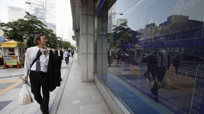 A man looks at an electronic board outside a brokerage in Tokyo
