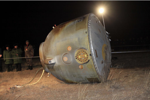 In this photo released by China's Xinhua News Agency, the re-entry capsule of Shenzhou 8 spacecraft lies on its side at a landing site located in Siziwang Banner in north China's Inner Mongolia Autonomous Region, Thursday, Nov. 17, 2011. The unmanned Chinese spacecraft returned to Earth on Thursday night after it docked twice with an orbiting module in preparation for the country launching its own space station. (AP Photo/Xinhua, Li Gang) NO SALES