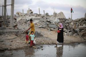 Palestinians walk next to ruins of houses, which witnesses said were destroyed during Israeli offensive, on fifth day of ceasefire in Khan Younis in Gaza Strip