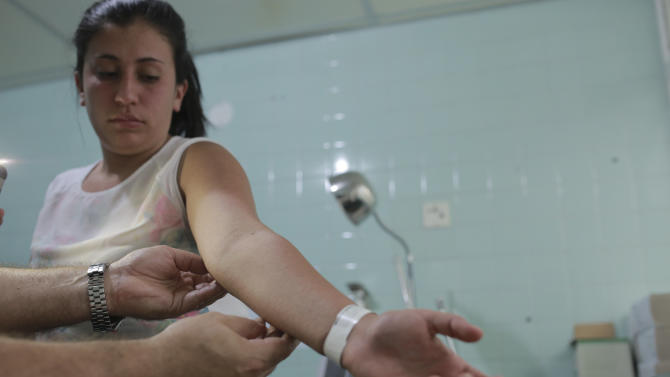A gynecologist examines a rash on the arm of six-weeks pregnant Daniela Rodriguez, 19, who was diagnosed with the Zika virus at the Erasmo Meoz Hospital in Cucuta, Colombia, Thursday, Feb. 11, 2016. The most common symptoms of Zika are fever, rash, joint pain, or conjunctivitis. (AP Photo/Ricardo Mazalan)