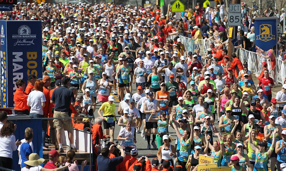 Runners make their way across the start line of the 116th running of the Boston Marathon, in Hopkinton, Mass., Monday, April 16, 2012. (AP Photo/Stew Milne)