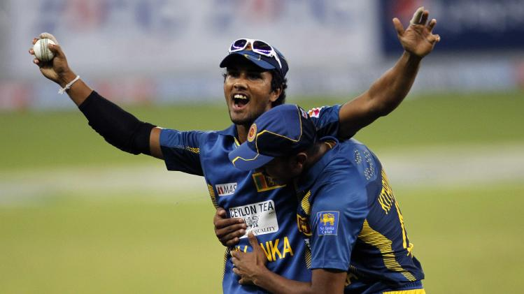 Sri Lanka's Dinesh Chandimal celebrates after taking a catch to dismiss Pakistan's Sohaib Maqsood during their second Twenty20 international cricket match in Dubai