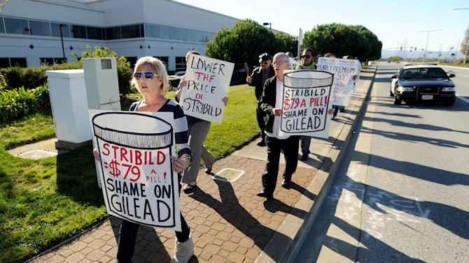 """About 40 protesters from across the country converged on Gilead Sciences headquarters in Foster City, Calif., on Wednesday, Nov. 14, 2012, calling on the drug maker to lower prices for its Stribild AIDS medication. Joined by an 18-wheel tractor trailer adorned with a """"Stop Corporate Welfare for Gilead"""" sign, picketers marched through streets around the company's headquarters for about an hour. (Noah Berger /AP Images for AIDS Healthcare Foundation)"""