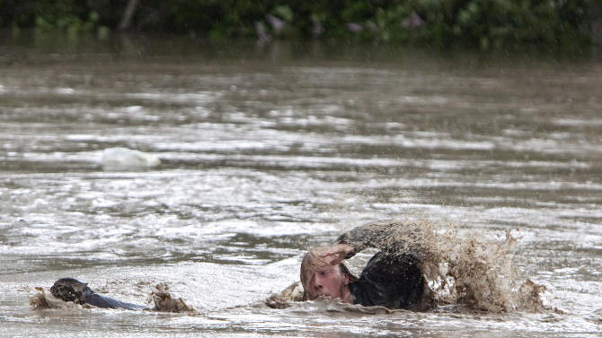 Kevan Yaets swims after his cat Momo to safety as the flood waters sweep him downstream and submerge the cab in High River, Alberta on June 20, 2013 after the Highwood River overflowed its banks. Hundreds of people have been evacuated with volunteers and emergency crews helping to aid stranded residents.