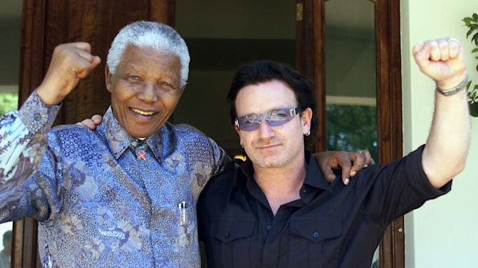FILE - In this May 25, 2002 file photo, Irish rock star Bono, right, and former South African President Nelson Mandela pose after meeting at Mandela's residence at Houghton in Johannesburg, South Africa. Heroic in his deeds, graceful in his manner, sainted in his image, Nelson Mandela long served as both cause and muse in the entertainment community. From the 1960s, when he was a political prisoner and South Africa was under the laws of apartheid, right up to recent times, when the racist laws of the land had fallen and he was among the world's most admired people, Mandela inspired concerts, songs, poems, fiction and movies. (AP Photo/Juda Ngwenya, File)