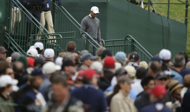 Tiger Woods makes his way to the ninth tee to start his first round of the U.S. Open Championship golf tournament Thursday, June 14, 2012, at The Olympic Club in San Francisco. (AP Photo/Charlie Riedel)