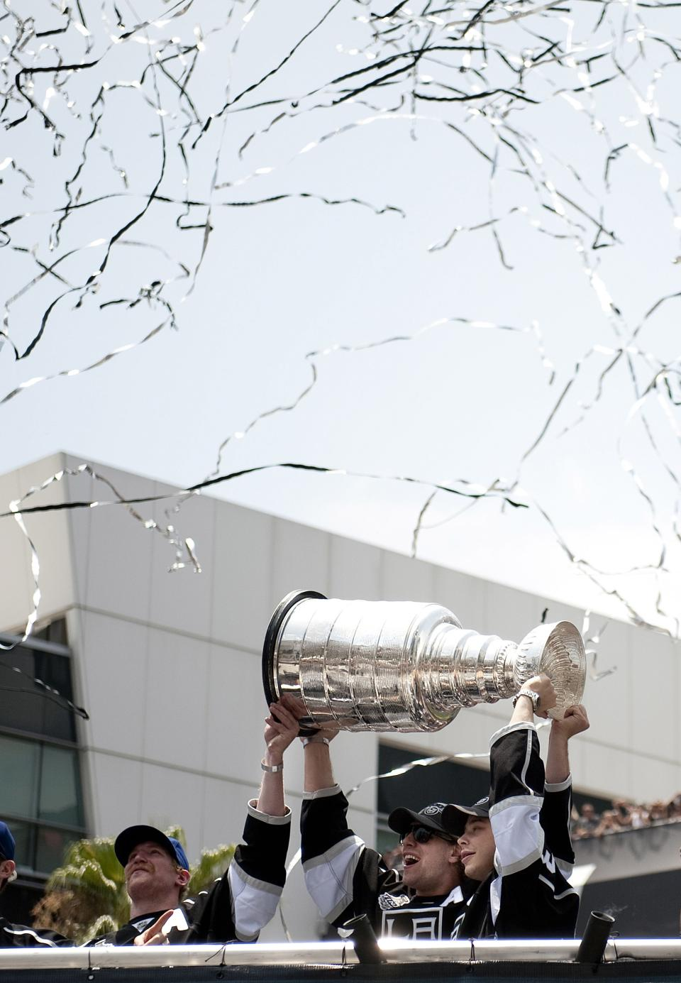 Confettie falls as  Los Angeles Kings players, from left, Matt Greene, Anze Kopitar and Dustin Brown hold up the Stanley Cup during a parade and rally celebrating the team's NHL hockey Stanley Cup championship in Los Angeles, Thursday, June 14, 2012.  (AP Photo/Grant Hindsley)