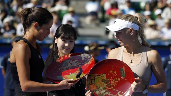 Ivanovic of Serbia and Wozniacki of Denmark look at their trophies during an award ceremony after their Pan Pacific Open women's singles final tennis match in Tokyo