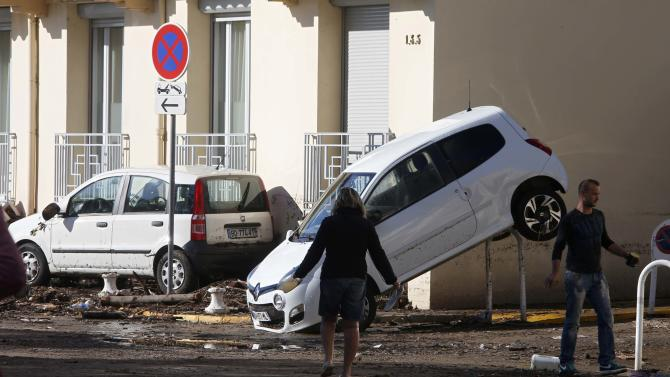 People look at cars which were damaged after flooding caused by torrential rain in Cannes
