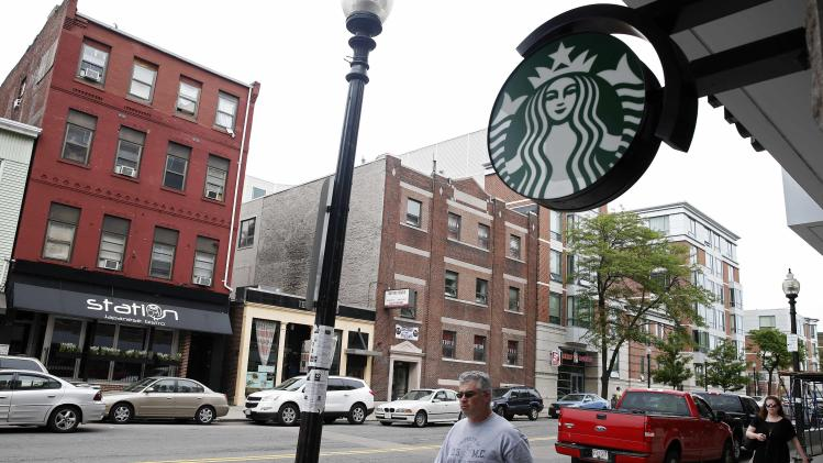 "The logo on a new Starbucks is seen across the street from the building, left, which once housed the Triple O's bar in the South Boston neighborhood of Boston, Thursday, June 6, 2013. Four decades after Boston crime boss James ""Whitey"" Bulger first rose to power, ""Southie"" is not what it used to be. The once blue-collar, Irish-Catholic neighborhood, is now an ethnic melting pot that has been invaded by young urban professionals who have gentrified the area and smoothed out its once-rough edges. (AP Photo/Michael Dwyer)"