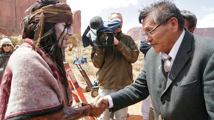 "This April 2012 photo released by the Navajo Nation shows, actor Johnny Depp shaking hands with Navajo Nation President Ben Shelly in Monument Valley during the filming of ""The Lone Ranger."" The Pendleton blanket was presented to Johnny Depp as a good will gesture on behalf of the Navajo Nation.  (AP Photo/Emerald Craig/Navajo Nation)"
