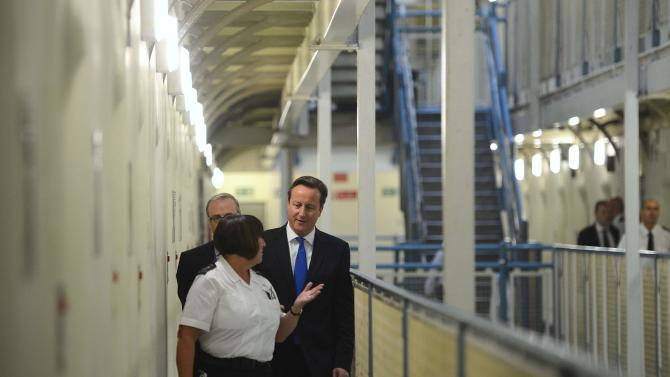 Britain's Prime Minister David Cameron, right, is escorted around C wing by prison officer Margaret Vaughan, during his visit to Wormwood Scrubs Prison, west London, Monday, Oct. 22, 2012. Cameron tried to put a week of heavy political criticism behind him as he visited a prison in west London Monday, seeing first hand his vision of charities, voluntary groups and private companies providing rehabilitation services to lower reoffending rates. (AP Photo/Paul Hackett, Pool)