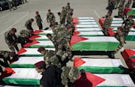 Palestinian security forces carry flag-draped coffins during preparations for the funeral procession of 91 Palestinians whose remains were returned by Israel in the West Bank city of Ramallah on Thursday. Some of the men died more than 40 years ago, officials say