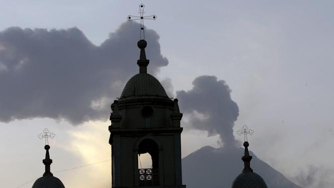 Church steeples are silhouetted against the active Tungurahua volcano, seen from Huambalo, Ecuador, Monday, Dec. 17, 2012.  The country's National Geophysics Institute says that a constant plume of gas and ash is rising about half a mile (1 kilometer) above the crater, with ash falling on nearby communities.  (AP Photo/Dolores Ochoa)