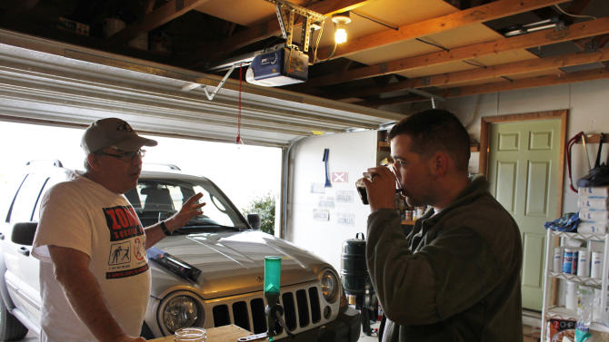 In this Dec. 24, 2012 photo, over three weeks back home from the war in Afghanistan, U.S. Army 1st Lt. Aaron Dunn drinks a beer in his garage with a neighbor to stopped by to say hello on Christmas Eve, in Fountain, Colo. Getting back to the routines and simple pleasures of his American life has been a joy for Aaron. (AP Photo/Brennan Linsley)