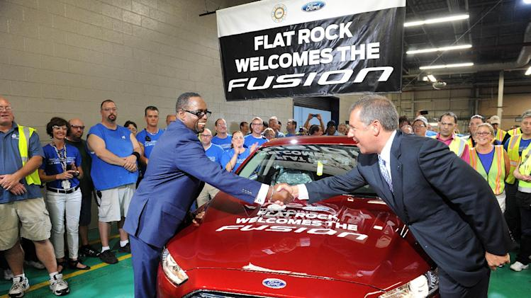 Jimmy Settles, UAW vice president, left, shakes hands with Joe Hinrichs, Ford president of the Americas, over a new 2014 Ford Fusion in Flatrock, Mich. on Thursday, Aug. 29, 2013. For the first time, Ford is making its Fusion sedan in the U.S. The company's Flat Rock, Mich., plant began making the Fusion on Thursday. (AP Photo/Detroit News, Charles V. Tines)