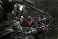 Armed Syrian men, members of the rebel Free Syrian Army, gather in a mountainous area of the restive Idlib province in northwestern Syria. Syrian President Bashar al-Assad responded Tuesday to UN-Arab League proposals for an end to the bloodshed in Syria even as monitors said nearly 50 more people were killed and a pro-regime daily reported the capture of a rebel city