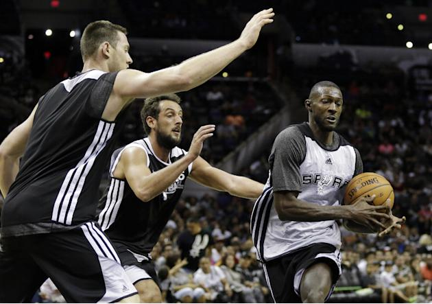 San Antonio Spurs' Courtney Fells, right, is defended by Spurs' Aron Baynes, left, of Australia, and Marco Belinelli, of Italy, during an open NBA basketball practice on Sunday, Oct. 6, 2013, in San A