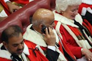 A peer uses an mobile smartphone in the Chamber of the House of Lords as he waits to hear Britain's Queen Elizabeth II read the Queen's Speech during the State Opening of Parliament in the Palace of Westminster in London. Queen Elizabeth II voiced the ruling coalition's bid to offer economic hope and win back voters after its worst few weeks yet in her annual address to parliament