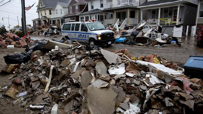 An New York Police Department van drives along a street soaked with rain and covered with debris in a Rockaway neighborhood of the borough of Queens, New York, Wednesday, Nov. 7, 2012, as a nor'easter aggravates already bad conditions in the wake of Superstorm Sandy. (AP Photo/Craig Ruttle)