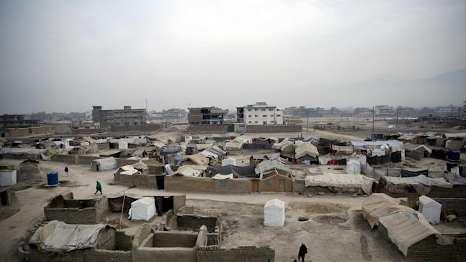 In this Wednesday, Dec. 24, 2014 photo, internally displaced Afghans walk in a camp in Kabul, Afghanistan. Thousands of Afghans are pouring into makeshift camps in the capital where they face a harsh winter as the Taliban return to areas once cleared by foreign forces, who this week are marking the end of their combat mission. (AP Photo/Massoud Hossaini)