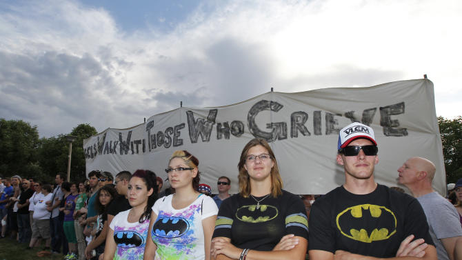 "Drew Griffith, right, and cousin Paige Morris, second from right, both from Aurora, wear Batman shirts, Sunday, July 22, 2012, in Aurora, Colo., during a prayer vigil for the victims of Friday's mass shooting at a movie theater. Twelve people were killed and dozens were injured in a shooting attack early Friday at the packed theater during a showing of the Batman movie, ""The Dark Knight Rises."" Police have identified the suspected shooter as James Holmes, 24. (AP Photo/Alex Brandon)"