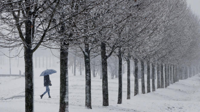 A women strolls through a small park in Frankfurt, Germany, Saturday, Dec. 27, 2014.  Snow and cold temperatures are forecasted for the next days all over Germany. (AP Photo/Michael Probst)