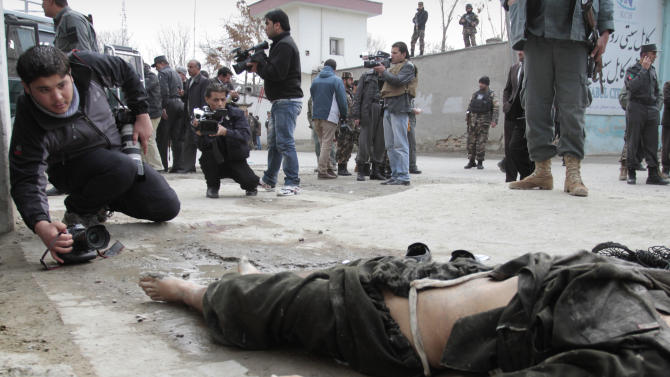 A photographer and a video cameraman film an insurgent's body at the scene where he was shot to death near an Afghan intelligence office in Kabul, Afghanistan, Sunday, Feb. 24, 2013. A series of early morning attacks hit eastern Afghanistan Sunday, with three separate suicide bombings in outlying provinces and a shootout between security forces and a would-be attacker in the capital city of Kabul. (AP Photo/Musadeq Sadeq)