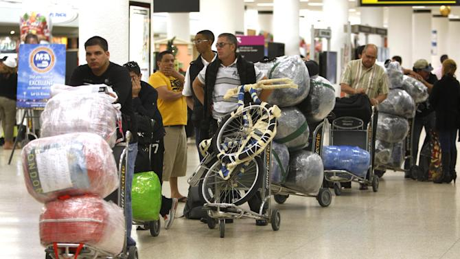 FILE - In this Dec. 19, 2011, file photo, travelers wait in line with their luggage at Miami International Airport before traveling Cuba in Miami. The door for travel to Cuba cracked open during President Barack Obama's first term. Cuban-Americans can now visit family on the island as often as they like. Americans can travel legally as part of an academic or religious trip. Perhaps it's for this reason that Obama's standing with the Cuban-American community in Florida stayed largely steady on Election Day, even though the modest openings with Cuba have riled some of South Florida's more conservative exiles. Exit polling showed that 49 percent of Cuban-Americans voted for the Democrat, roughly the same percentage as four years ago. (AP Photo/Lynne Sladky, File)