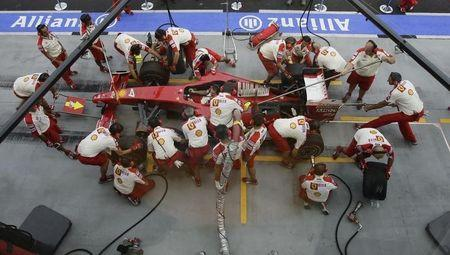 Crew members of the Ferrari Formula One team practise pit stops prior to the start of the third practice session of the Singapore F1 Grand Prix at the Marina Bay street circuit