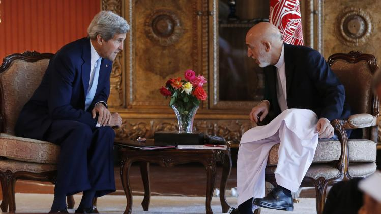 U.S. Secretary of State Kerry leans in to speak with Afghanistan's incumbent President Karzai at the presidential palace in Kabul