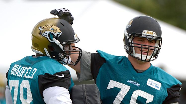 Jacksonville Jaguars offensive linemen Cameron Bradfield (78) and Luke Joeckel (76) acknowledge each other after competing in a drill during NFL football training camp in Jacksonville, Fla., Friday, July 25, 2014
