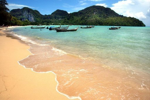 <p>Boats moored off a beach in southern Thailand on July 24, 2002. A 22-year-old British tourist was shot dead as he danced at a New Year party on one of Thailand's most famous islands after a fight between rival Thai gangs erupted on the beach, police said on Tuesday.</p>