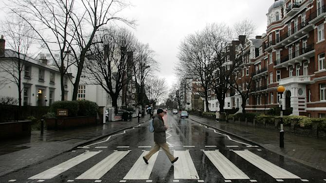 """FILE - In this file photo taken Feb. 16, 2010, a man walks on the zebra crossing  made famous from the album cover of The Beatles' 'Abbey Road' in front of Abbey Road Studios, seen at left, in London. It's a mystery tour, but it's hardly magical. More than nine miles from the striped crosswalk made famous by the Beatles album """"Abbey Road,"""" this drab transit station in east London keeps drawing confused fans of the Fab Four into unwanted jaunts through a gritty, industrial area just south of London' Olympic Stadium. Abbey Road Station has no relation to the Beatles' Abbey Road Studios, the birth place of the eponymous album and a London tourist landmark. The glass-and-metal station is wedged between a train depot, warehouses, and gloomy public housing projects, a world away from the leafy, suburban street pictured on the album's cover.  (AP Photo/Akira Suemori, File)"""