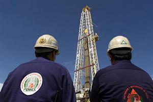 Two engineers with Mexico's state owned oil company, PEMEX (Petroleos de Mexico), watch work on an o..