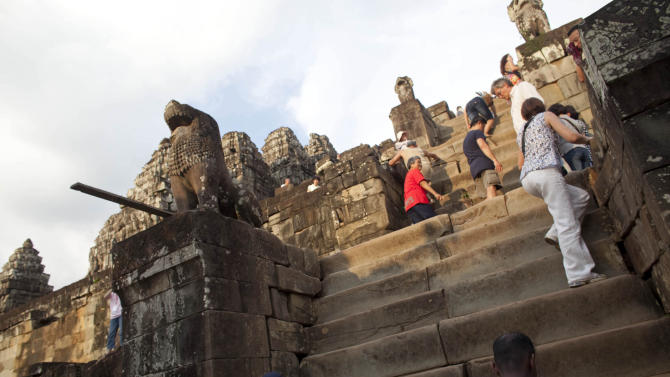 In this photo taken on May 11, 2011, Western tourist and others climb to the top of the 10th century temple Bakheng in the Angkor Wat complex near Siem Reap, Cambodia, to view the setting sun.  A traffic jam of up to 3,000 tourists surges up a steep hillside, trampling over vulnerable stonework and quaffing beer at a sacred hilltop that provides spectacular sunset views of the massive beehive-like towers rising from the main temple in this ancient city: Angkor Wat. Cambodian Tourism Minister Thong Khon says some 6 million visitors per year are projected by 2020. (AP Photo/David Longstreath)
