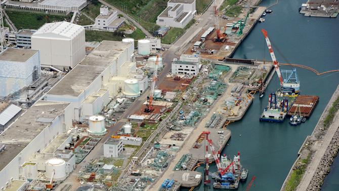 "This aerial photo taken on July 9, 2013 shows reactor buildings Unit 2, left, and Unit 1 at Fukushima Dai-ichi nuclear power plant in Okuama, Fukushima Prefecture, northern Japan. Japan's nuclear regulator says radioactive water from the crippled Fukushima power plant is probably leaking into the Pacific Ocean, a problem long suspected by experts but denied by the plant's operator. Officials from the Nuclear Regulation Authority said a leak is ""strongly suspected"" and urged plant operator Tokyo Electric Power Co. to determine where the water may be leaking from and assess the environmental and other risks, including the impact on the food chain. The watchdog said Wednesday, July 10, 2013 it would form a panel of experts to look into ways to contain the problem. (AP Photo/Kyodo News) JAPAN OUT, MANDATORY CREDIT"