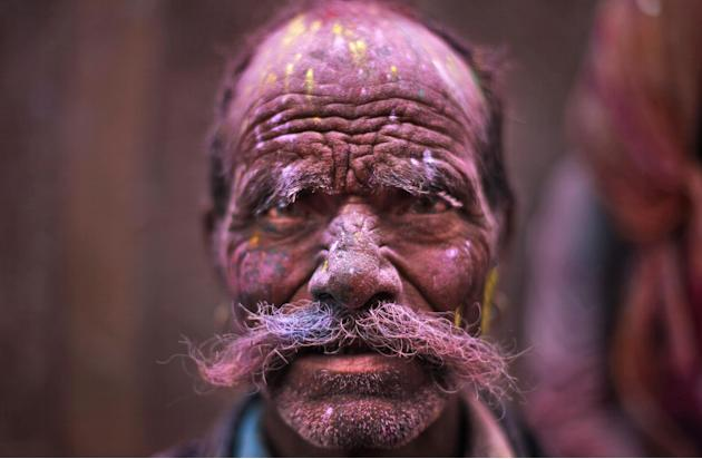 A Hindu devotee, face smeared with colored powder, leaves the Banke Bihari temple during Holi celebrations in Vrindavan, India, Wednesday, March 27, 2013. Holi, the Hindu festival of colors that also