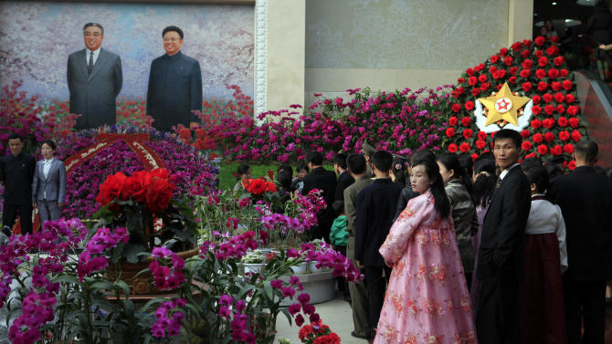 """A couple looks back as they stand in line to pose for a picture in front of portraits of the late leaders Kim Il Sung and Kim Jong Il at a festival for the """"Kimilsungia"""" flower to mark 100 years since the birth of North Korea's late leader in Pyongyang, North Korea, Tuesday, April 17, 2012. (AP Photo/Ng Han Guan)"""