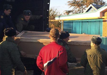 Russian servicemen unload a coffin containing the body of Kostenko from a truck near his family's house in the village of Grechnaya Balka