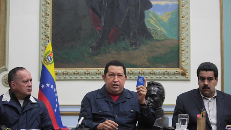 In this photo released by Miraflores Press Office, Venezuela's President Hugo Chavez, center, holds up a copy of national constitution as President of the Assembly Diosdado Cabello, left, and Vice- President Nicolas Maduro looks on   during a televised speech form his office at Miraflores Presidential palace in Caracas, Venezuela, Saturday, Dec. 8, 2012. Chavez announced Saturday night that his cancer has returned and that he will undergo another surgery in Cuba. Chavez, who won re-election on Oct. 7, also said for the first time that if his health were to worsen, his successor would be Vice President Nicolas Maduro.(AP Photo/Miraflores Press Office, Marcelo Garcia)