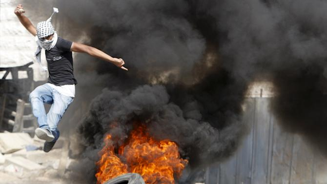 Palestinian jumps over burning tyres during clashes with Israeli troops in Hebron