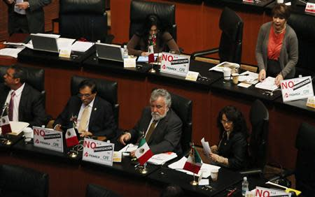 Senator Dolores Padierna and Senator Alejandro Encinas of the Party of the Democratic Revolution sit next to other senators of PRD before a debate on an energy reform bill at the Senate in Mexico City