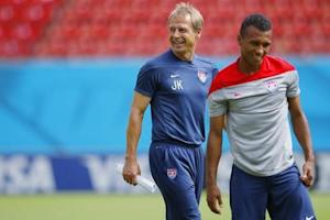 U.S. national soccer team head coach Klinsmann smiles as his team, including midfielder Julian Green, stretch during a training session at the Pernambuco arena in Recife