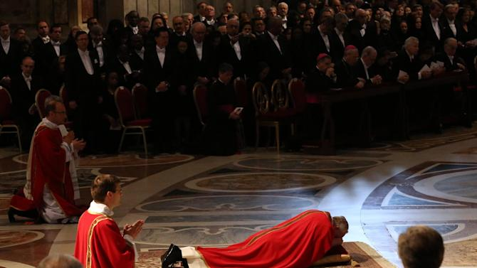 Pope Francis lies down in prayer during the Passion of Christ Mass inside St. Peter's Basilica, at the Vatican, Friday, March 29, 2013. Pope Francis began the Good Friday service at the Vatican with the Passion of Christ Mass and hours later will go to the ancient Colosseum in Rome for the traditional Way of the Cross procession. (AP Photo/Gregorio Borgia)