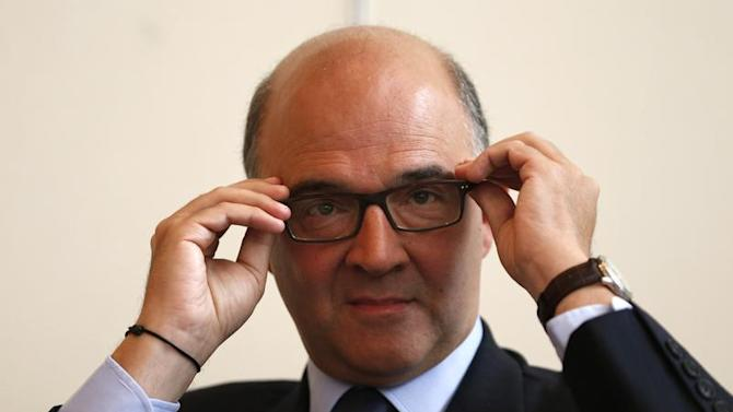 French Finance Minister Pierre Moscovici adjusts his glasses during a news conference on the 2014 budget at the Economy ministry in Paris