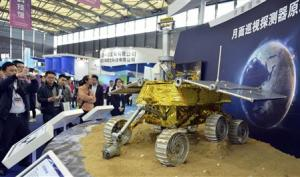 Visitors take pictures of a prototype model of a lunar rover at the 15th China International Industry Fair in Shanghai