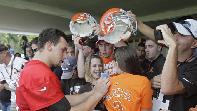 Cleveland Browns quarterback Johnny Manziel signs autographs for fans after his first practice at the NFL football team's training camp in Berea, Ohio on Saturday, July 26, 2014. (AP Photo)